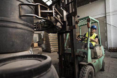 Worker inside cabin lift machine, barrels - JASF000896