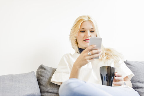 Blond young woman sitting on couch with cup of coffee looking at smartphone - FMOF000043