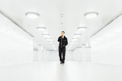 Teenager walking through an empty subway tunnel while talking on the phone in Berlin - MMF001284