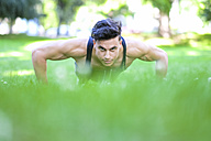 Young man doing push-ups in meadow - SIPF000566