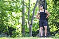 Athlete leaning against tree - SIPF000569