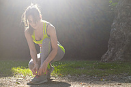 Sportswoman lacing her shoes in park - SIPF000572