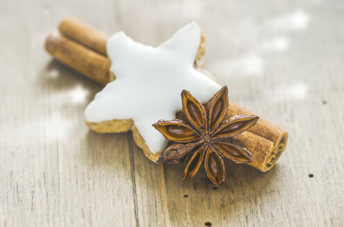 Home-baked cinnamon star, cinnamon sticks and star anise on wood - ODF001396