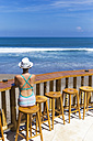 Indonesia, Bali, Young woman sitting on bar stool at the beach - KNTF000416