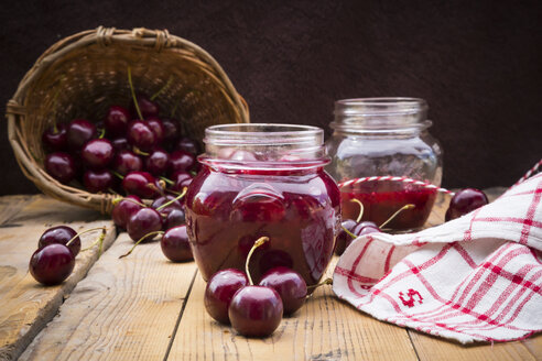 Glasses of homemade cherry groats, dish towel and cherries on wood - LVF005067