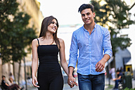 Happy young couple walking hand in hand - SIPF000577