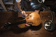 Luthier adjusting the sound post of a violin in his workshop - ABZF000787