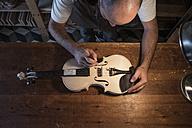 Luthier adjusting the sound post of an unvarnished violin in his workshop - ABZF000790