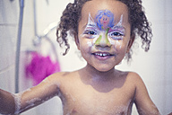 Portrait of smiling little girl with painted face in a bath - YNF000014