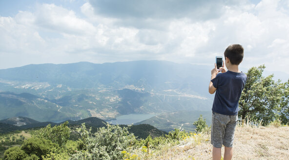 Greece, Central Macedonia, boy taking smartphone picture in the mountains - DEGF000861
