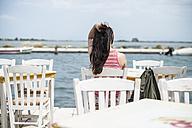 Greece, Lefkada, woman sitting in a Greek taverna by the sea - DEGF000864