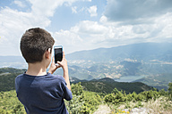 Greece, Central Macedonia, boy taking smartphone picture in the mountains - DEGF000870
