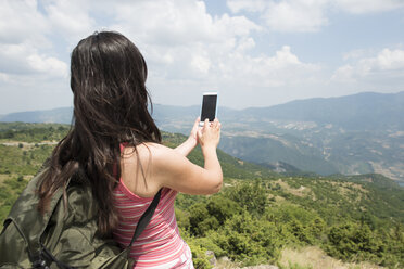 Greece, Central Macedonia, woman taking smartphone picture in the mountains - DEGF000873