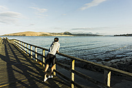 New Zealand, Whangamata, back view of man on a jetty - UUF007930