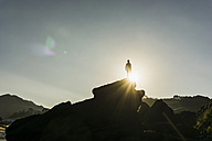 Silhouette of man standing on a rock at backlight - UUF007933