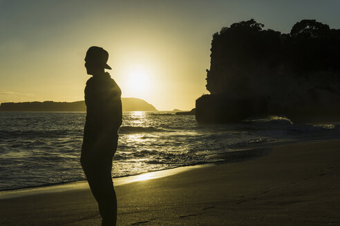 New Zealand, Wanganui, silhouette of man standing on the beach looking to the sea - UUF007942