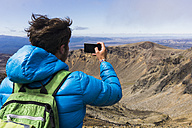 New Zealand, Tongariro National Park, back view of hiker taking a photo with smartphone - UUF007948