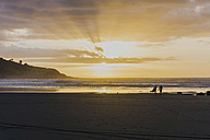 Silhouettes of two people with surfboards on the beach at twilight - UUF007957