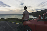 Back view of tourist leaning against car looking to the sea - UUF007969