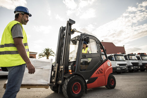 Woman in forklift talking to foreman of construction company - JASF000915
