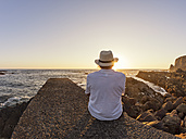 Portugal, Senior man sitting on wall at harbour at sunset - LAF001663
