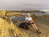 Portugal, Senior man sitting at beach, reading book - LAF001666