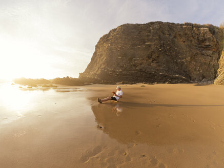 Portugal, Senior man sitting at beach, reading book - LAF001672