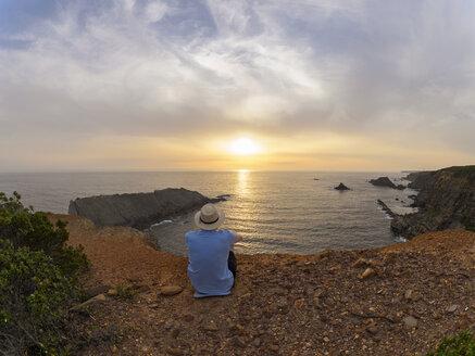 Portugal, Senior man sitting at bay watching sunset - LAF001678