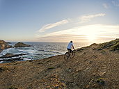 Portugal, Senior man mountain biking at the sea - LAF001681