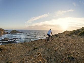Portugal, Senior man mountain biking at the sea - LAF001681