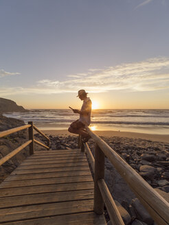 Portugal, Senior man sitting on railing at the beach, reading - LAF001687