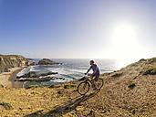 Portugal, Senior man mountain biking at the sea - LAF001693