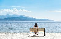 Greece, Sergoulas, woman sitting on bench at the coast - DEGF000899