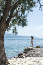 Greece, Sergoulas, woman taking pictures with smartphone at the coast - DEGF000902