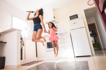 Playful teenage girl with her little sister in kitchen pretending to sing into microphone - SIPF000632