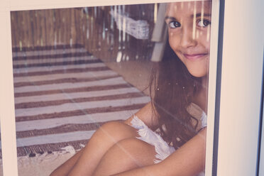Portrait of smiling little girl sitting behind window - SIPF000638
