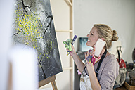 Female painter in front of canvas, smartphone - ZEF008884