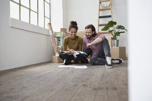 Couple sitting on floor of new flat choosing from color samples - RBF004592