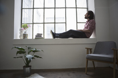 Man sitting on window sill looking out of window - RBF004613