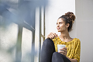 Young woman sitting on window sill with a cup of coffee - RBF004637