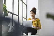 Man sitting on window sill using laptop - RBF004640