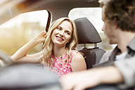 Portrait of smiling blond woman sitting on passenger seat in a car talking to her friend - PESF000190