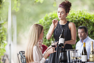 Waitress showing wine bottle to woman in restaurant - ZEF008901
