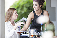 Waitress serving wine and chocolates in restaurant - ZEF008916