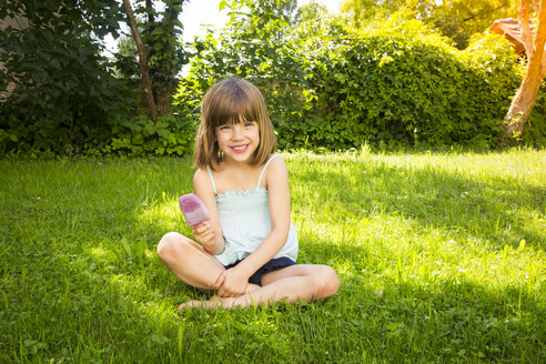 Portrait of happy little girl sitting on a meadow with blueberry ice lolly - LVF005085