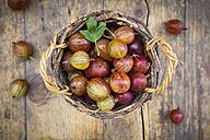 Wickerbasket of red gooseberries on wood - LVF005088