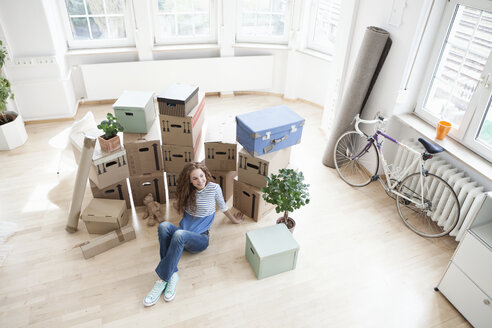 Woman surrounded by cardboard boxes sitting on floor - RBF004677
