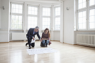 Real estate agent showing construction plan to client in empty apartment - RBF004680