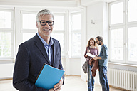 Portrait of smiling real estate agent with couple in background - RBF004683