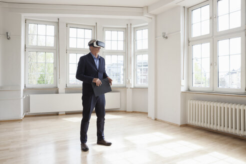Real estate agent wearing virtual reality glasses in empty apartment - RBF004686
